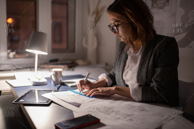 Overworked architect creating draft in dark office