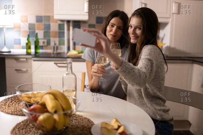 Young ladies taking selfie with wine