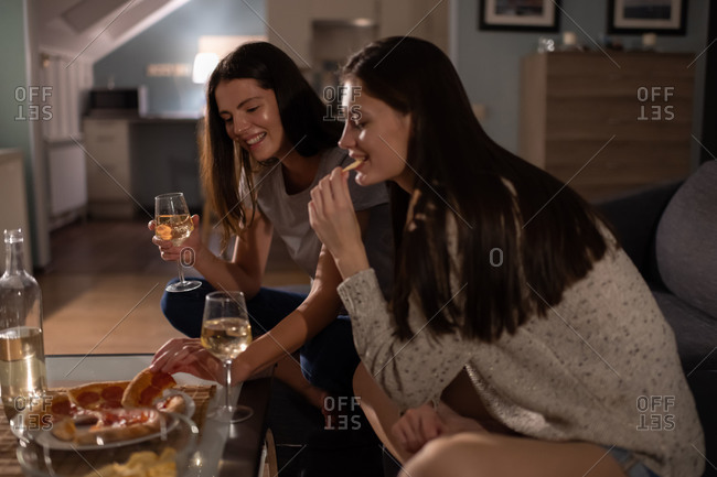 Cheerful women drinking wine and eating pizza on sofa