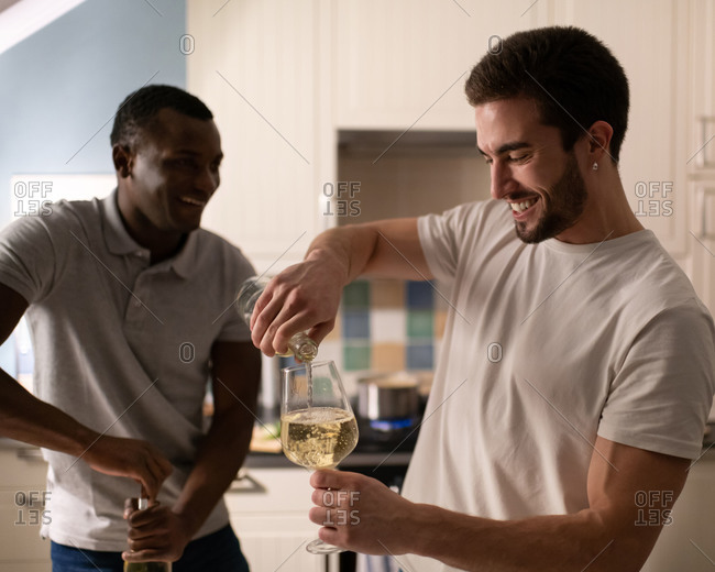 Diverse male friends preparing wine for home party