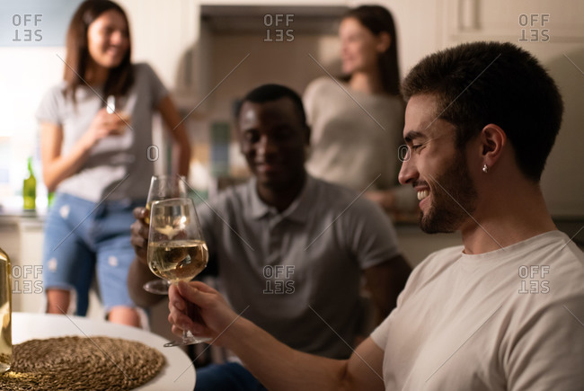 Happy guy enjoying wine during friends party