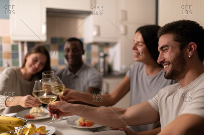 Cheerful guy clinking glasses with diverse friends