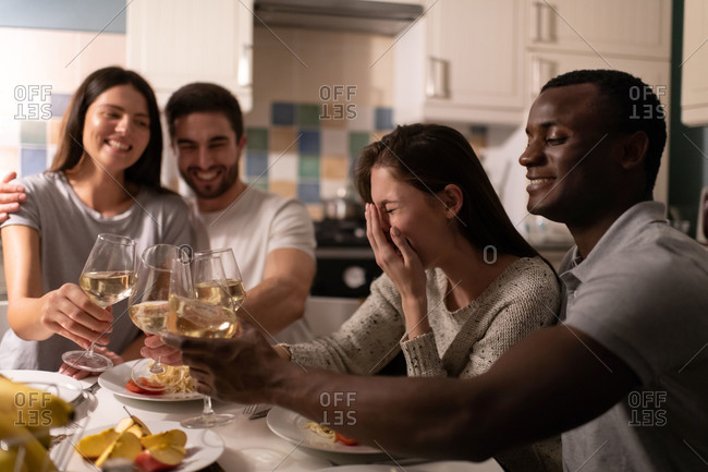 Young woman laughing while drinking wine with friends and black boyfriend