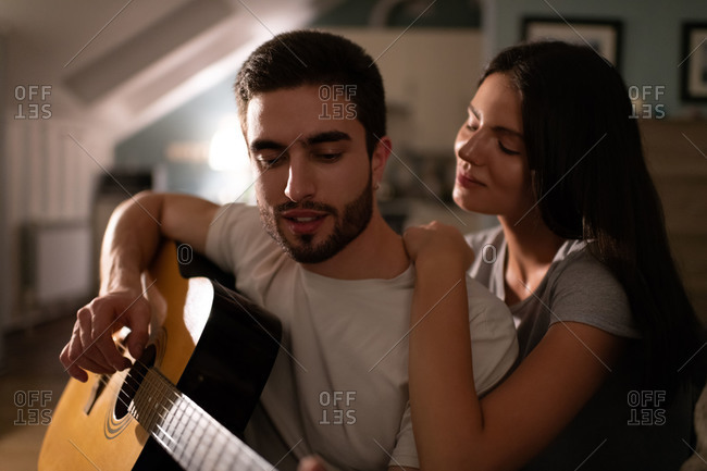 Young man playing guitar for girlfriend