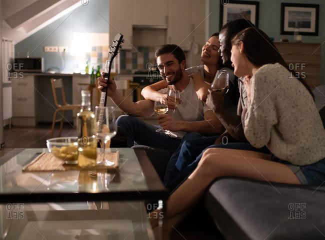 Multiethnic friends drinking wine in living room
