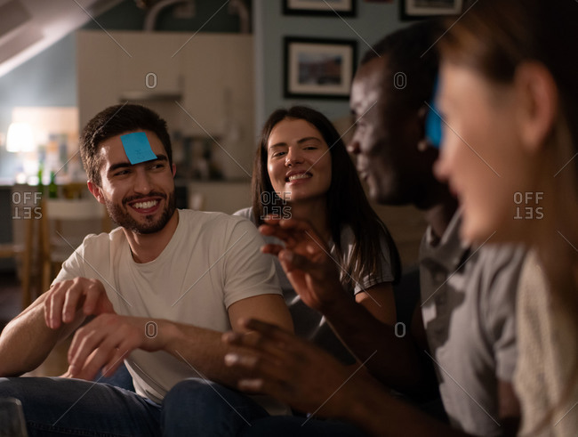 Cheerful guy playing guessing game with friends