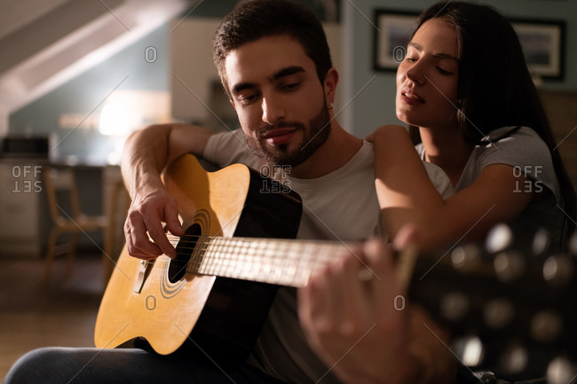 Young woman listening to boyfriend playing guitar