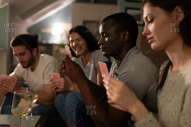 African American guy playing cards with friends
