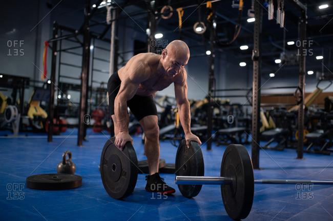 Muscular senior athlete preparing barbell for training