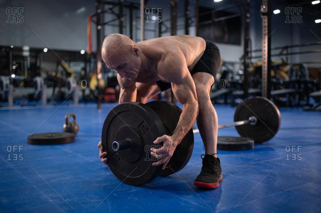 Bald elderly sportsman preparing barbell for training