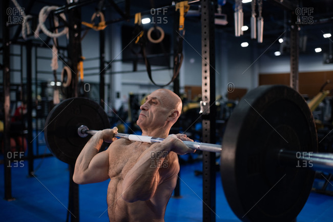 Strong senior man lifting barbell in gym