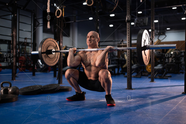 Concentrated aged man squatting with heavy barbell
