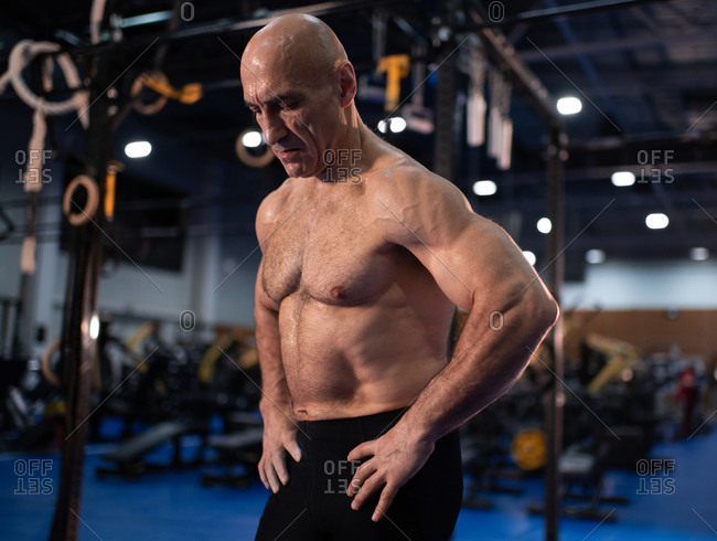 Muscular aged man resting during functional workout