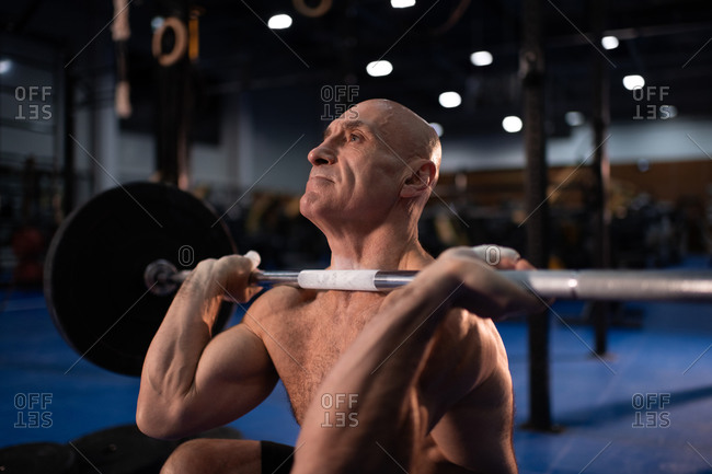 Bald senior sportsman squatting with heavy barbell