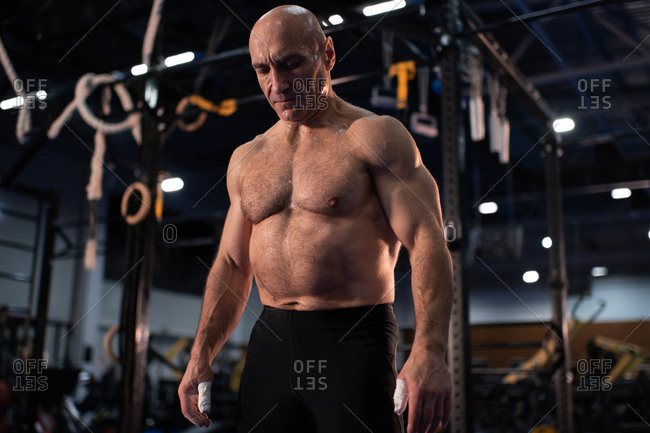 Muscular old sportsman resting in gym