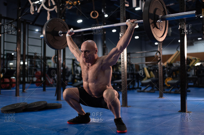 Muscular aged man squatting with barbell in gym
