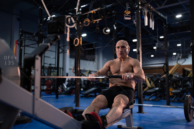 Powerful aged man exercising on rowing machine