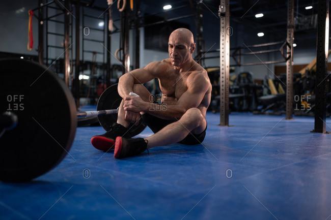 Muscular senior athlete resting during weightlifting training