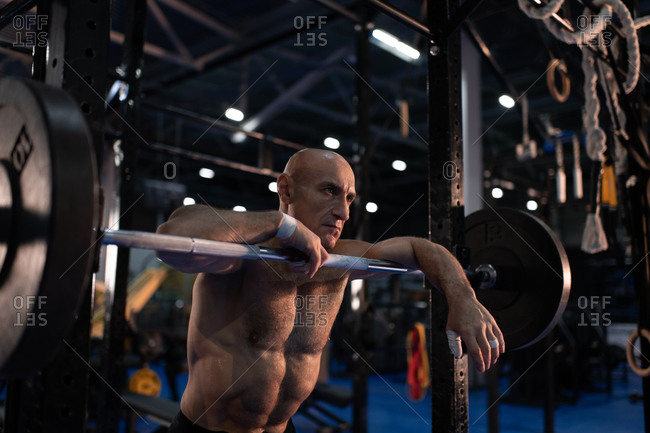Shirtless aged athlete leaning on barbell