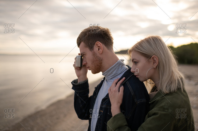 Man photographer with girlfriend on lake coast