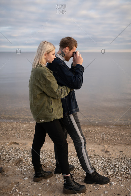 Young couple with photo camera standing on lake shore