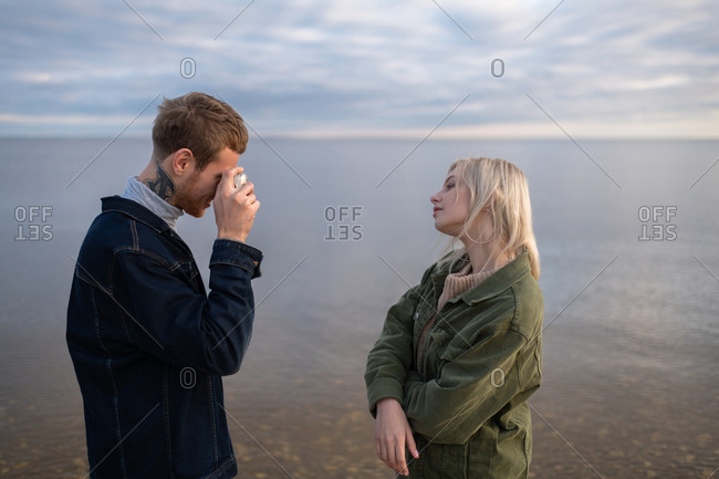 Photographer taking pictures of girlfriend near water