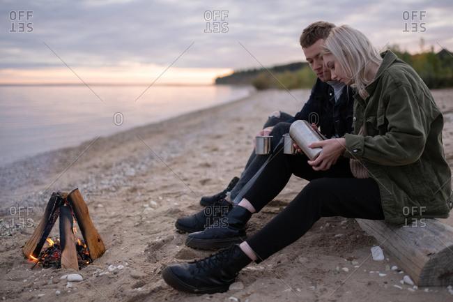 Woman pouring tea to boyfriend near bonfire