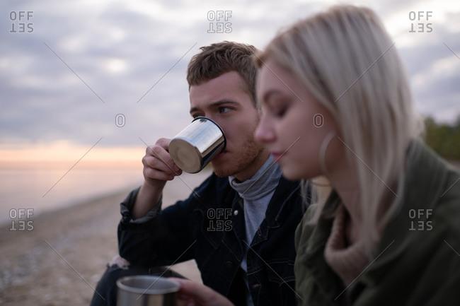 Man drinking tea near girlfriend in countryside