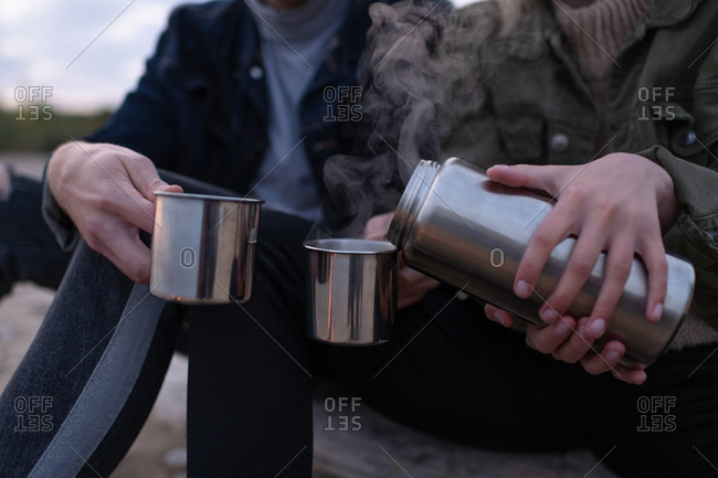 Crop couple sharing steamy tea in countryside