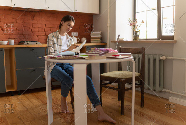 Woman studying and highlighting text at home
