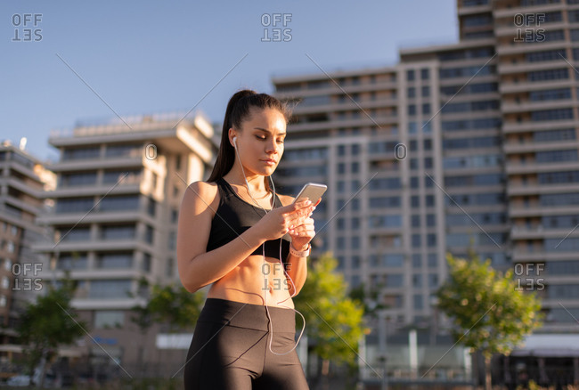 Young woman using smartphone during workout