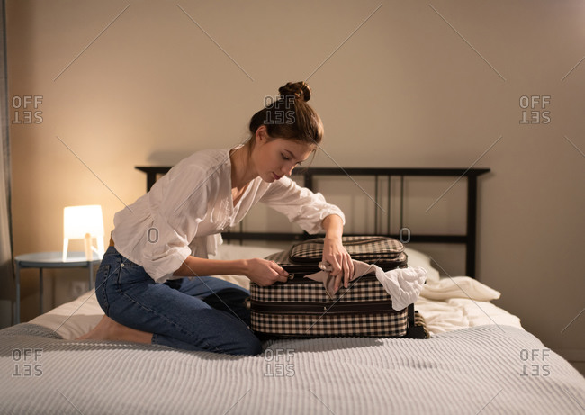 Young woman closing suitcase on bed