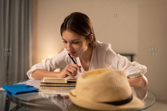 Dreamy young female planning trip abroad