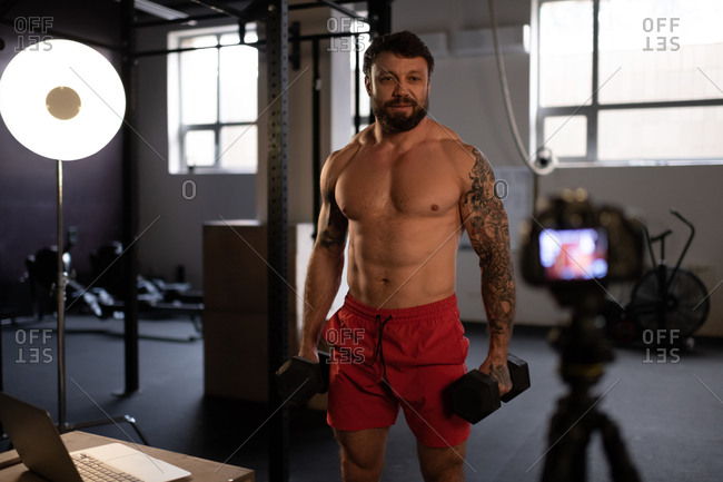 Confident trainer with dumbbells shooting video for vlog
