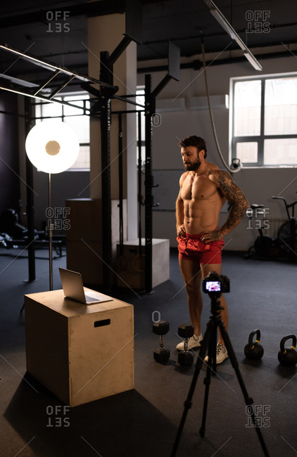 Muscular sportsman preparing for remote fitness training