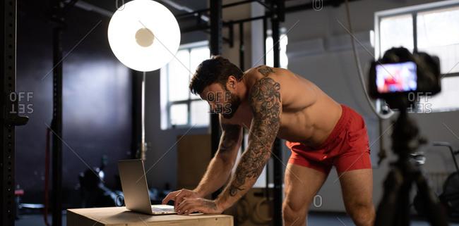 Strong athlete typing on laptop keyboard before webinar