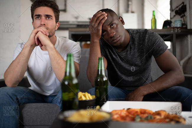 Unhappy diverse friends watching disappointing football match