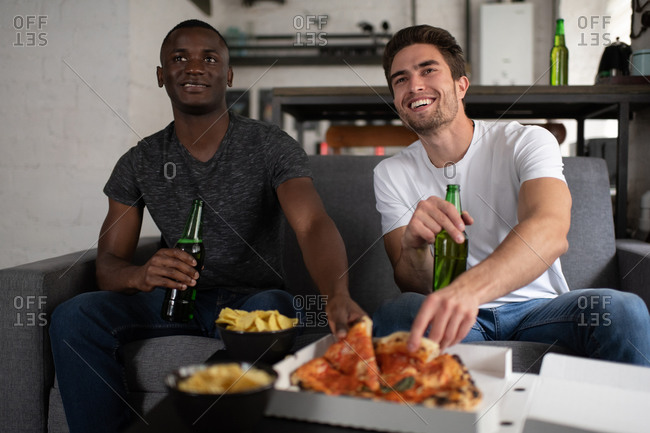 Cheerful multiethnic friends eating pizza and watching football match