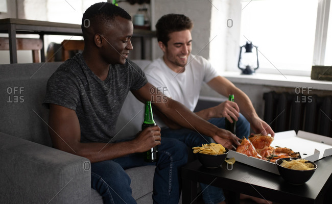Smiling diverse friends enjoying pizza and beer during football match