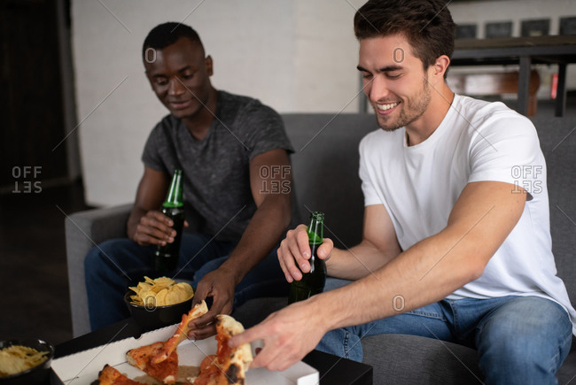 Cheerful multiethnic friends eating pizza and drinking beer