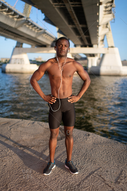Fit sportsman standing with earphones during workout