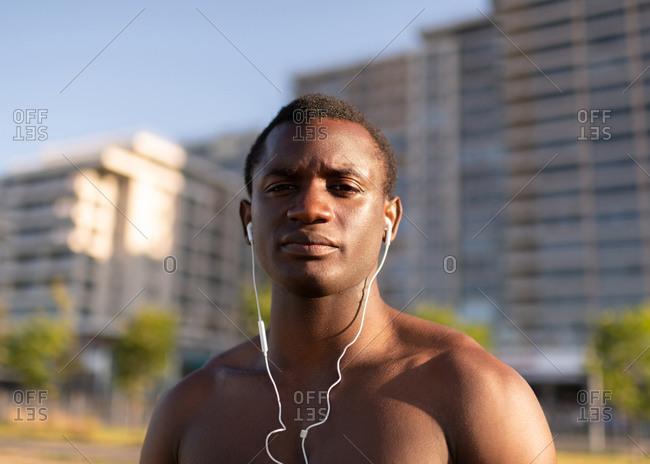 Handsome muscular black sportsman with earphones outside