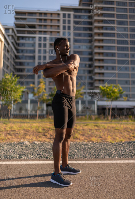 Athletic black male warming up body on sports ground