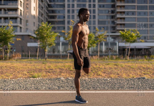 Sportive African American male warming up body before running