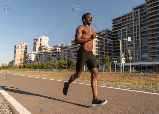 Active black sportsman with earphones focusing on running