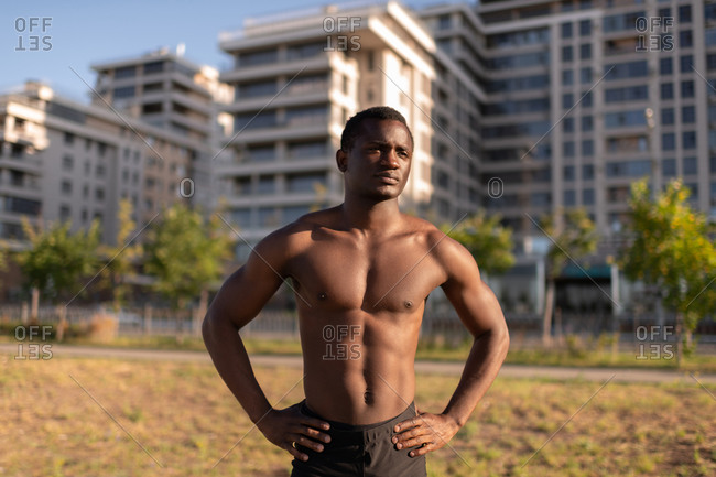 Determined athletic black male with naked in sunlight on street