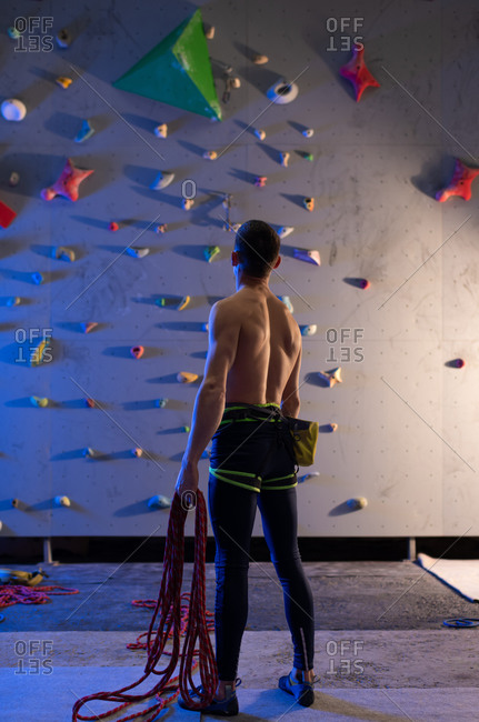 Anonymous climber examining wall during workout