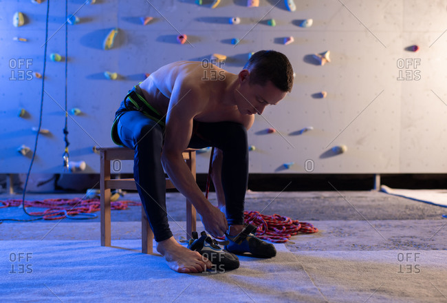 Young climber putting on shoes near wall
