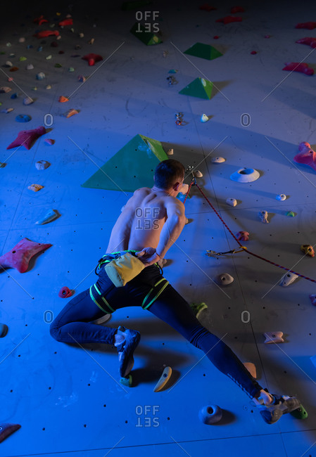 Unrecognizable rock climber using magnesium bag on wall