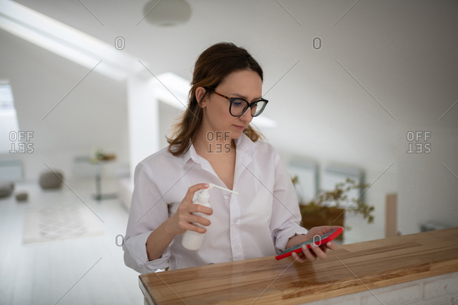 Young woman disinfecting smartphone at home